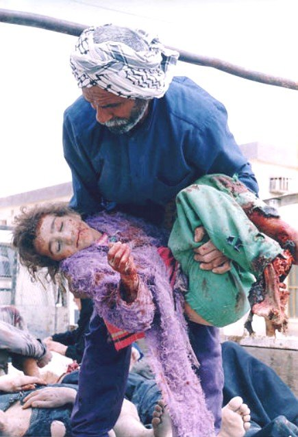 Iraqi man carrying a bloodied Iraqi child